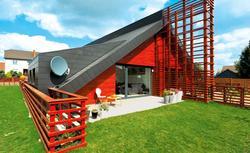 Oryginalny dom bliźniak. Czerwona elewacja i dach do samej ziemi